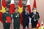 Vietnamese Defense Minister Phan Van Giang, center left, and Japanese Defense Minister Nobuo Kishi, center right, stand for photo with their officials after signing an agreement in Hanoi, Vietnam Sunday, Sept. 12, 2021. Japan can now give defense equipment and technology to Vietnam under an agreement signed Saturday, as the two countries step up their military cooperation amid worries about China's growing military influence. (Nguyen Trong Duc/VNA via AP)