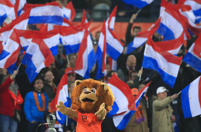 FILE - In this Netherlands Thursday, March 21, 2019 filers, fans wait for the start of the Euro 2020 group C qualifying soccer match between Netherlands and Belarus at the Feyenoord stadium in Rotterdam, Netherlands. With games scattered across 11 cities from London to Baku, this year's European Championship is going to be hard on the fans. Amid the coronavirus pandemic, it remains to be seen how many supporters will be able to attend matches or if any can follow their teams across borders into different countries. (AP Photo/Peter Dejong, File)