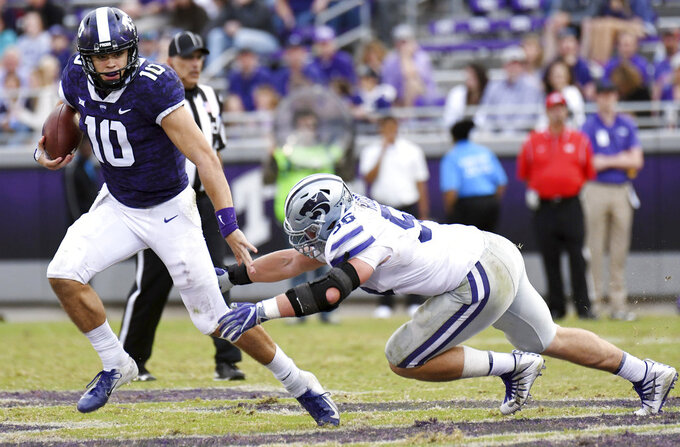 TCU quarterback Mike Collins, left, scrambles to avoid Kansas State's Wyatt Hubert during the fourth quarter of an NCAA college football game Saturday, Nov. 3, 2018, in Fort Worth, Texas. (Bob Haynes/Star-Telegram via AP)