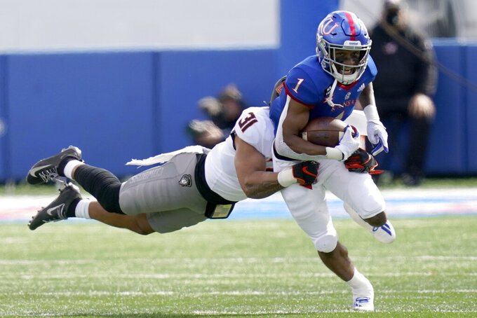 Kansas running back Pooka Williams Jr. (1) is tackled by Oklahoma State safety Kolby Harvell-Peel (31) during the first half of an NCAA college football game in Lawrence, Kan., Saturday, Oct. 3, 2020. (AP Photo/Orlin Wagner)