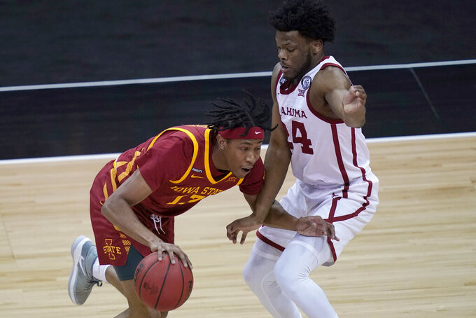 Iowa State forward Javan Johnson (13) drives on Oklahoma guard Elijah Harkless (24) during the first half of an NCAA college basketball game in the first round of the Big 12 men's tournament in Kansas City, Mo., Wednesday, March 10, 2021. (AP Photo/Orlin Wagner)