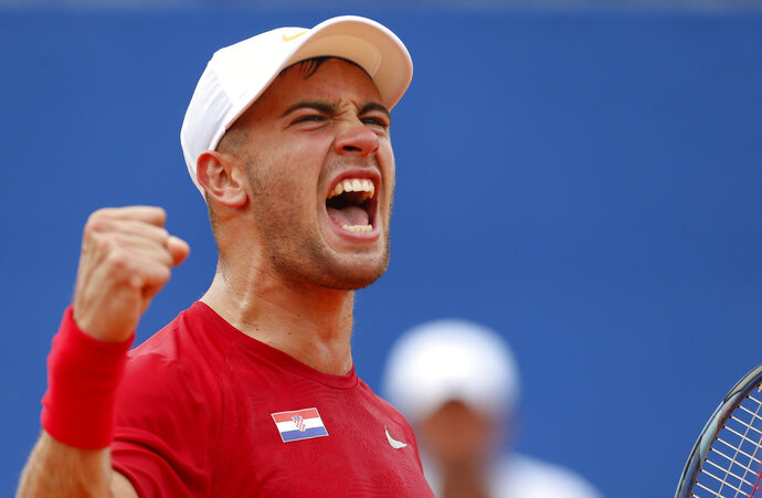 Borna Coric of Croatia celebrates after winning the second set as he plays against Steve Johnson of the United States during a Davis Cup semifinal singles tennis match between Croatia and the United States in Zadar, Croatia, Friday, Sept. 14, 2018. (AP Photo/Darko Bandic)