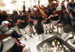 Atlanta Braves manager Brian Snitker, center, is doused by his players as they celebrate after defeating Philadelphia Phillies 5-3 in a baseball game to clinch the National League East Division, Saturday, Sept. 22, 2018, in Atlanta.. (AP Photo/John Bazemore)