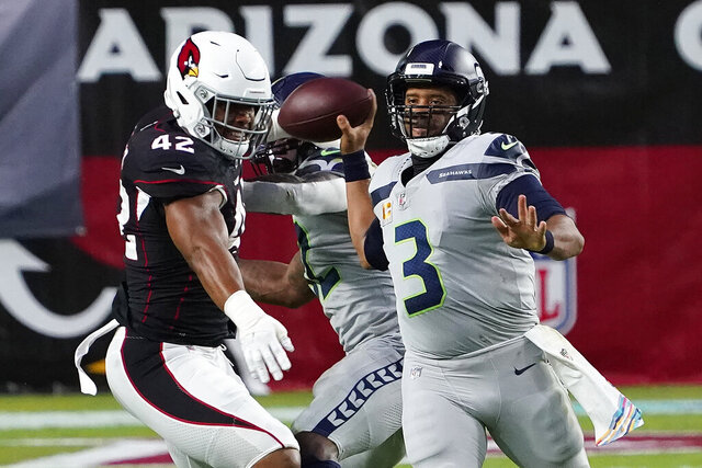 Seattle Seahawks quarterback Russell Wilson (3) throws as Arizona Cardinals outside linebacker Devon Kennard (42) defends during the first half of an NFL football game, Sunday, Oct. 25, 2020, in Glendale, Ariz. (AP Photo/Rick Scuteri)