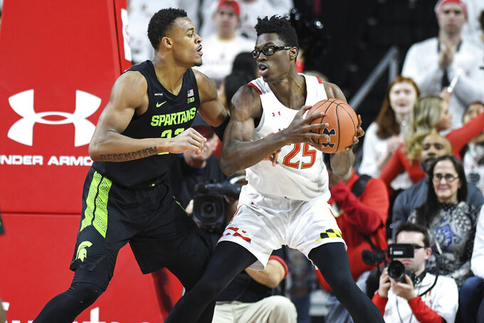 Maryland forward Jalen Smith (25) handles the ball against Michigan State forward Xavier Tillman Sr. (23) during the first half of an NCAA college basketball game Saturday, Feb. 29, 2020, in College Park, Md. (AP Photo/Terrance Williams)