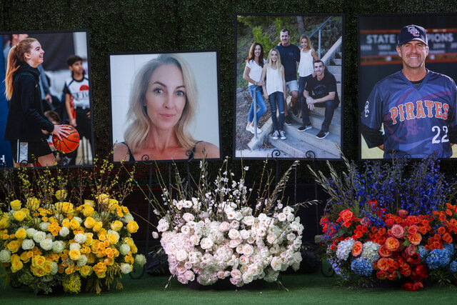 Flowers and photos honor members of the Altobelli family outside Angel Stadium, Monday, Feb. 10, 2020, in Anaheim, Calif. Coach John Altobelli, 56, far right, his wife, Keri, 43, second from left, and his daughter Alyssa, 13, left, died in a helicopter crash on Jan. 26 in Calabasas. (AP Photo/Damian Dovarganes)