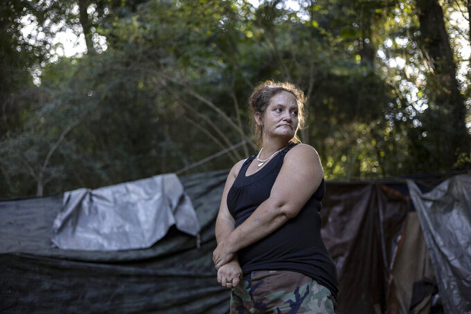 """Flora Harlow, who has been in and out of permanent housing over the past several years, poses near her tent on Thursday, Sept. 9, 2021, in Athens, Ga. Harlow and others live in a small encampmentcolloquially called """"Cooterville,"""" a wooded area under CSX's train tracks off Willow Street that is scheduled to be clearedby Nov. 12. (Kayla Renie/Athens Banner-Herald via AP)"""