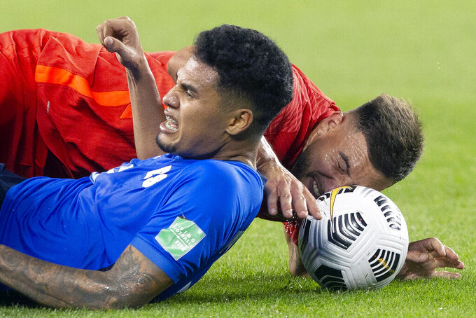 Canada's Lucas Cavallini, right, and El Salvador's Ronald Rodriguez go to ground as they battle for the ball during the second half of a World Cup qualifying soccer match Wednesday, Sept. 8, 2021, in Toronto. (Chris Young/The Canadian Press via AP)