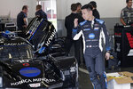 Kamui Kobayashi walks by his car in his garage before a practice session during testing for the upcoming Rolex 24 hour auto race at Daytona International Speedway, Friday, Jan. 3, 2020, in Daytona Beach, Fla. (AP Photo/John Raoux)