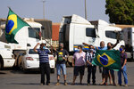 Truck drivers supporting Brazilian President Jair Bolsonaro wave flags as they gather at a gas station just south of Brasilia, Brazil, Thursday, Sept. 9, 2021. Bolsonaro rallied supporters two days prior to coincide with Independence Day but truckers remain mobilized. (AP Photo/Eraldo Peres)