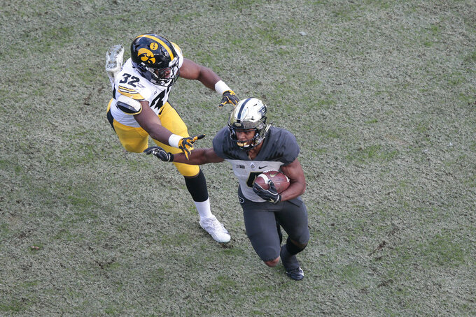 Purdue wide receiver Rondale Moore (4) runs from Iowa linebacker Djimon Colbert (32) in the first half of an NCAA college football game in West Lafayette, Ind., Saturday, Nov. 3, 2018. Purdue won 38-36. (AP Photo/AJ Mast)