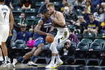 Minnesota Timberwolves forward Noah Vonleh (1) drives on Indiana Pacers forward Domantas Sabonis during the first half of an NBA preseason basketball game in Indianapolis, Tuesday, Oct. 15, 2019. (AP Photo/Michael Conroy)