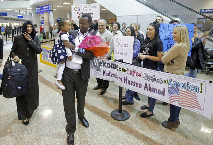FILE - This Feb. 10, 2017, file photo, Abdisellam Hassen Ahmed, a Somali refugee who had been stuck in limbo after President Donald Trump temporarily banned refugee entries, walks with his wife Nimo Hashi, and his 2-year-old daughter, Taslim, who he met for the first time after arriving at Salt Lake City International Airport.  Refugee advocates, including faith-based groups that President Donald Trump is courting in his re-election bid, called on Congress Thursday, Oct. 1, 2020, to halt his administration's plans to slash the limit on refugees allowed into the U.S. to a record low, saying it goes against America's values.   (AP Photo/Rick Bowmer, File)