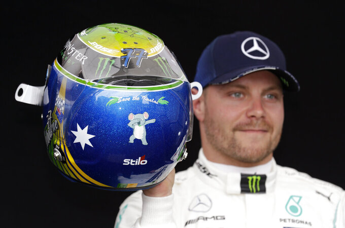 Mercedes driver Valtteri Bottas of Finland shows his helmet with a koala painted on it as he poses for a photo at the Australian Formula One Grand Prix in Melbourne, Thursday, March 12, 2020. (AP Photo/Rick Rycroft)