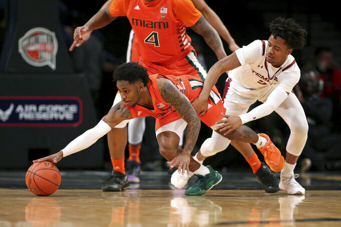 Miami guard Chris Lykes, left, reaches for the ball against Temple guard Monty Scott during the first half of an NCAA college basketball game at Barclays Center, Tuesday, Dec. 17, 2019, in New York. (AP Photo/Michael Owens)