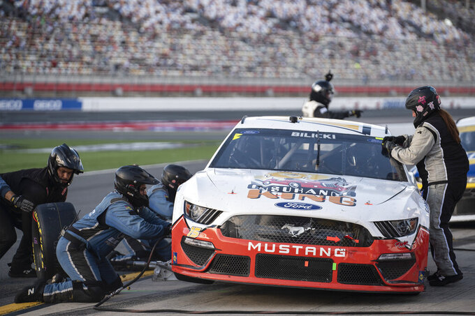 Crew members change tires during a pit stop for Josh Bilicki (15)during a NASCAR Cup Series auto racing race at Charlotte Motor Speedway, Monday, Oct. 11, 2021, in Concord, N.C. (AP Photo/Matt Kelley)