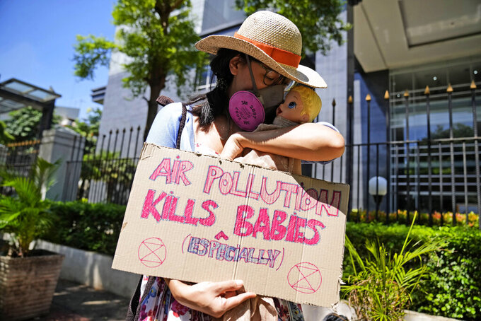 An activist displays a placard with a doll representing babies affected by air pollution during a protest outside Central Jakarta District Court where judges are scheduled to announce their verdict on a civil lawsuit filed against several Indonesian officials, including President Joko Widodo and Jakarta Governor Anies Baswedan, for their failure to improve poor air quality in the capital city, in Jakarta, Indonesia, Thursday, Sept. 16, 2021. (AP Photo/Dita Alangkara)