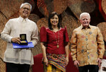 Philippine Vice President Leonor Robredo, center, and Ramon Magsaysay Chair, Board of Trustees, Jose Cuisia Jr., right, pose with this year's Ramon Magsaysay awardee Filipino Raymundo Pujante Cayabyab during ceremonies in Manila, Philippines on Monday Sept. 9, 2019. Five people are being honored as this year's winners of the Ramon Magsaysay Awards, regarded as Asia's version of the Nobel Prize, including a South Korean who helped fight bullying and suicide and a Thai housewife who became a human rights defender after losing her husband to violence in southern Thailand. (AP Photo/Aaron Favila)