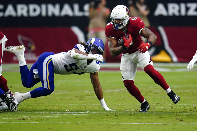Arizona Cardinals running back James Conner (6) eludes the tackles of Minnesota Vikings middle linebacker Eric Kendricks during the second half of an NFL football game, Sunday, Sept. 19, 2021, in Glendale, Ariz. (AP Photo/Ross D. Franklin)