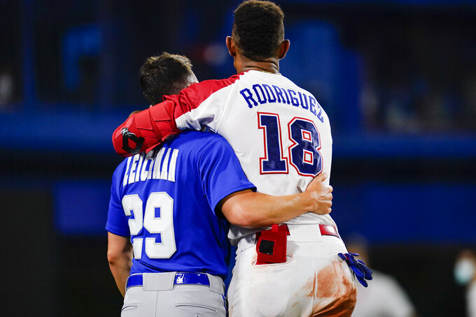 Israel's Alon Leichman, left, and the Dominican Republic's Julio Rodriguez embrace after a baseball game at the 2020 Summer Olympics, Tuesday, Aug. 3, 2021, in Yokohama, Japan. The Dominican Republic won 7-6. (AP Photo/Matt Slocum)