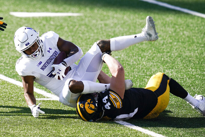 Northwestern wide receiver Kyric McGowan is tackled by Iowa linebacker Seth Benson (44) after catching a pass during the first half of an NCAA college football game, Saturday, Oct. 31, 2020, in Iowa City, Iowa. (AP Photo/Charlie Neibergall)