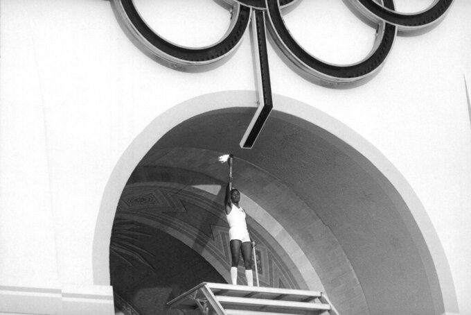 Rafer Johnson, 1960 gold medalist for the decathlon, lights the Olympic torch during the Opening Ceremonies of the 23rd Olympiad in Los Angeles in 1984. (AP Photo)