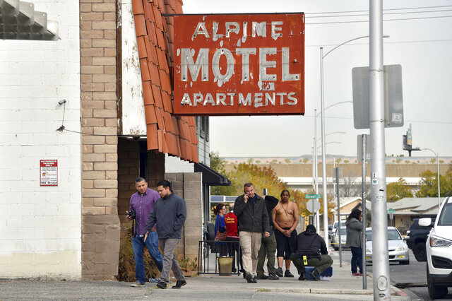FILE - In this Dec. 21, 2019, file photo, investigators work the scene of a fire at the three-story Alpine Motel Apartments in Las Vegas. Search warrant records show that investigators seized a computer and paperwork on Jan. 14, 2020, from the manager's office of the downtown Las Vegas apartment building where inspectors cited owners for code violations following a fire that killed six people and injured 13. No criminal charges have been filed in the ongoing probe of the deadly fire. (AP Photo/David Becker, File)