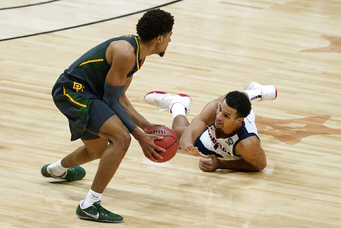 Baylor guard MaCio Teague, left, picks up a loose ball over Gonzaga guard Jalen Suggs, right, during the first half of the championship game in the men's Final Four NCAA college basketball tournament, Monday, April 5, 2021, at Lucas Oil Stadium in Indianapolis. (AP Photo/Darron Cummings)