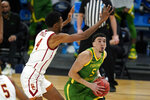 Oregon guard Chris Duarte (5) drives to the basket ahead of Southern California forward Evan Mobley (4) during the second half of a Sweet 16 game in the NCAA men's college basketball tournament at Bankers Life Fieldhouse, Sunday, March 28, 2021, in Indianapolis. (AP Photo/Jeff Roberson)