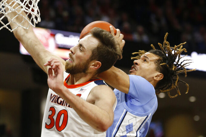 Virginia forward Jay Huff (30) and North Carolina guard Cole Anthony, right, collide under the basket during the first half of an NCAA college basketball game in Richmond, Va., Sunday, Dec. 8, 2019. (AP Photo/Steve Helber)