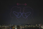 In this on Saturday, July 4, 2020, photo, some 400 drones fly over the Han River showing messages of appreciation for medical workers during the coronavirus pandemic in Seoul, South Korea. (Lim Hwa-young/Yonhap via AP)