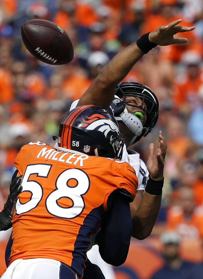 FILE - In this Sept. 9, 2018, file photo, Seattle Seahawks quarterback Russell Wilson, top, loses the ball as he is hit by Denver Broncos linebacker Von Miller (58) during the first half of an NFL football game, in Denver. Von Miller might be the only one at Broncos headquarters lamenting Khalil Mack's startling trade from the Oakland Raiders to the Chicago Bears.  (AP Photo/Jack Dempsey, File)