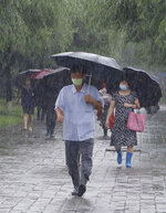 Pedestrians brave the torrential rains, Wednesday, August 5, 2020, in Pyongyang. North Korea says torrential rains have lashed the country, prompting outside worries about possible big damages in the impoverished country. (AP Photo/Cha Song Ho)