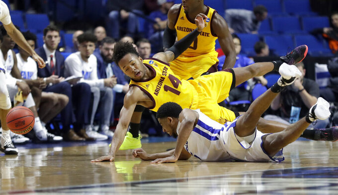 Arizona State's Kimani Lawrence (14) and Buffalo's CJ Massinburg collide while diving after a loose ball during the second half of a first round men's college basketball game in the NCAA Tournament Friday, March 22, 2019, in Tulsa, Okla. (AP Photo/Jeff Roberson)