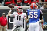 Georgia quarterback Jake Fromm (11) throws a pass over Florida defensive lineman Kyree Campbell (55) during the first half of an NCAA college football game, Saturday, Nov. 2, 2019, in Jacksonville, Fla. (AP Photo/John Raoux)