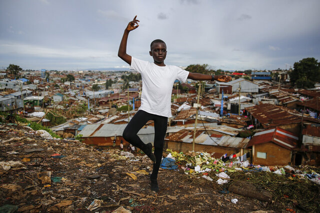 In this photo taken Thursday, April 23, 2020, ballet student Eugene Ochieng, 12, poses for a portrait in the Kibera slum, or informal settlement, of Nairobi, Kenya. The coronavirus pandemic is forcing children to stay home and learn remotely but in the depths of Kenya's slums, 12-year-old ballet student Eugene Ochieng faces huge obstacles to remote learning: no computer, no internet access and very little space to practice. (AP Photo/Brian Inganga)