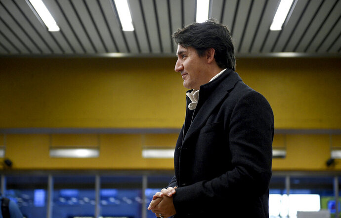 Canada's Prime Minister Justin Trudeau greets commuters at a metro station in Montreal, Tuesday, Oct. 22, 2019. Trudeau won a second term in Canada's national elections Monday, losing the majority but delivering unexpectedly strong results despite having been weakened by a series of scandals that tarnished his image as a liberal icon.  (Sean Kilpatrick/The Canadian Press via AP)