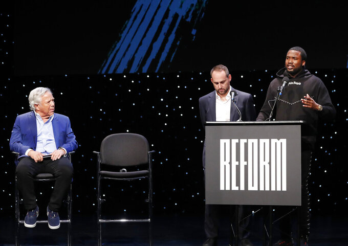 New England Patriots owner Robert Kraft, left, and Philadelphia 76ers owner and Fanatics executive chairman Michael Rubin, second from left, listen to recording artist Meek Mill talk abut being incarcerated at the launch of Reform Alliance, a partnership among entertainment moguls, recording artists, business and sports leaders who hope to transform the American criminal justice system, Wednesday, Jan. 23, 2019, in New York. (AP Photo/Kathy Willens)