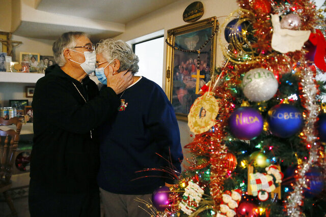 Roberto Mata gives his wife Mary Alice a kiss on the forehead by their Christmas tree Wednesday, Dec. 16, at their home in Chaparral, N.M. Roberto survived COVID-19 after spending 47 days at the Hospital of Providence Memorial Campus earlier this year. The Mata family says they are grateful for their health and for Roberto's recovery. (Briana Sanchez/The El Paso Times via AP)