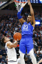 BYU forward Yoeli Childs (23) dunks against Utah State guard Diogo Brito (24) in the first half during an NCAA college basketball game Saturday, Dec. 14, 2019, in Salt Lake City. (AP Photo/Rick Bowmer)