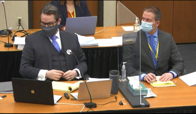 In this image from video, defense attorney Eric Nelson, left, and defendant, former Minneapolis police officer Derek Chauvin, right, listen, Wednesday, April 14, 2021, as Hennepin County Judge PeterCahill presides over motions in the trial of Chauvin at the Hennepin County Courthouse in Minneapolis. Chauvin is charged in the May 25, 2020 death of George Floyd.  (Court TV, via AP, Pool)