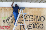 A man paints outside a store that was boarded up to prevent damage amid protests in San Juan, Puerto Rico, Thursday, July 18, 2019. Protesters are demanding Gov. Ricardo Rossello resign after the leak of online chats that show him making misogynistic slurs and mocking his constituents. (AP Photo/Dennis M. Rivera Pichardo)