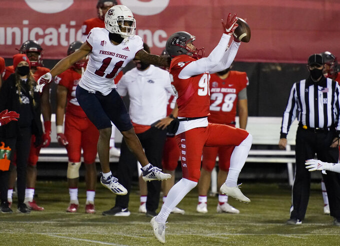 New Mexico's Tyson Dyer (96) grabs an onside kick attempt over Fresno State's Josh Kelly (11) during the second half of an NCAA college football game Saturday, Dec. 12, 2020, in Las Vegas. (AP Photo/John Locher)