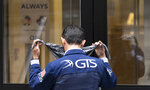 A stock trader puts on his mask before entering the New York Stock Exchange, Monday, Aug. 31, 2020, in New York. (AP Photo/Mark Lennihan)