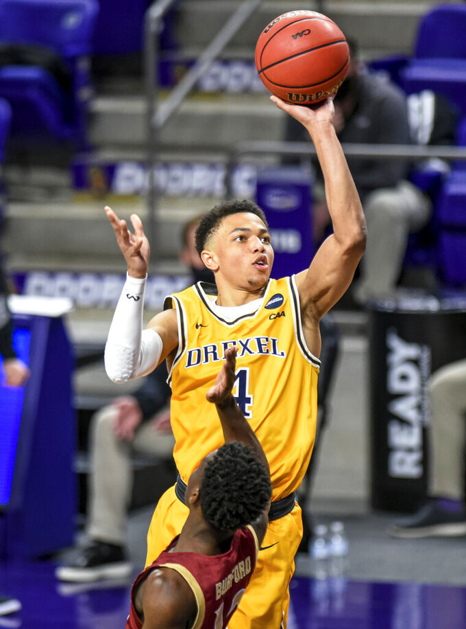 Drexel guard Xavier Bell (4) shoots over Elon guard Darius Burford (12) during the first half of an NCAA college basketball game for the Colonial Athletic Association men's tournament championship in Harrisonburg, Va., Tuesday, March 9, 2021. (AP Photo/Daniel Lin)