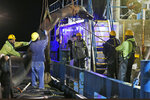 Workers prepare to attach suction hose to the menhaden fishing boat Windmill Point at Omega Protein's menhaden processing plant on Cockrell's Creek in Reedville, Va., Tuesday, Nov. 26, 2019.The last east coast fishery now produces fish oil for health supplements and faces a possible moratorium over concerns about overfishing in the Chesapeake Bay. (AP Photo/Steve Helber)