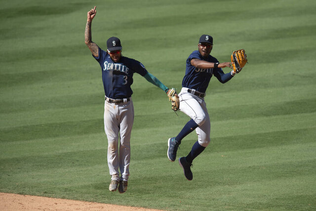 Seattle Mariners shortstop J.P. Crawford, left, and center fielder Kyle Lewis celebrate the team's win over the Los Angeles Angels in a baseball game in Anaheim, Calif., Monday, Aug. 31, 2020. (AP Photo/Kyusung Gong)