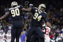 New Orleans Saints defensive end Cameron Jordan (94) and linebacker Tanoh Kpassagnon (90) celebrate a defensive stop in the first half of an NFL football game against the New York Giants in New Orleans, Sunday, Oct. 3, 2021. (AP Photo/Derick Hingle)