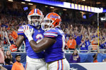 Florida running back Lamical Perine, left, celebrates with offensive lineman Nick Buchanan after scoring a touchdown during the first half of the Orange Bowl NCAA college football game against Virginia, Monday, Dec. 30, 2019, in Miami Gardens, Fla. (AP Photo/Lynne Sladky)