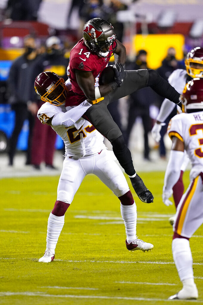 Tampa Bay Buccaneers wide receiver Chris Godwin (14) is grabbed from behind by Washington Football Team cornerback Ronald Darby (23) during the first half of an NFL wild-card playoff football game, Saturday, Jan. 9, 2021, in Landover, Md. (AP Photo/Andrew Harnik)